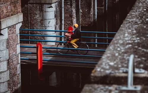 human man riding bicycle on gray concrete bridge during daytime person