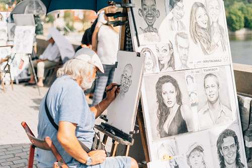 person man sitting on chair sketching a person's face human