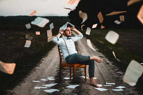 human man sitting on chair with book chair