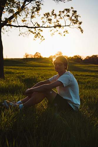 human man sitting on grass while resting hand on knee during golden hour person