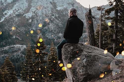 person man sitting on rock human