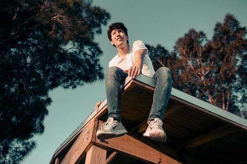 person man sitting on roof human