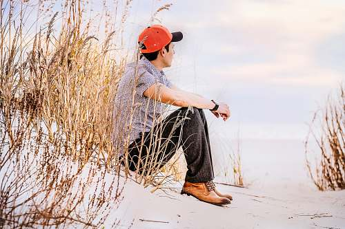 human man sitting on sand with wheat looking right during daytime person