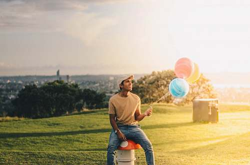 human man sitting while holding balloons person