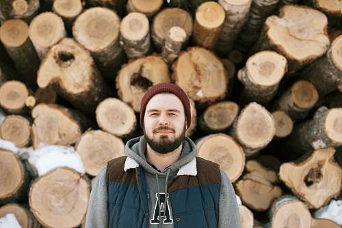 wood man standing behind firewoods lumber