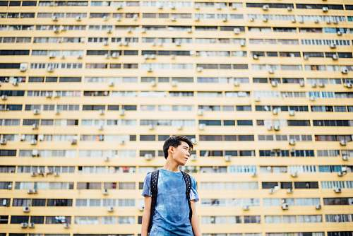 person man standing in front of skyscraper human