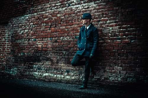 human man wearing black coat leaning on brown brick wall brick