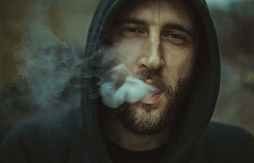 human man wearing black pullover hoodie blowing white smoke person