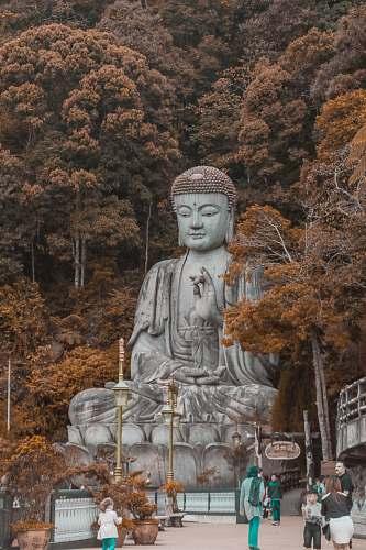 buddha people walking near buddha statue near trees at daytime art