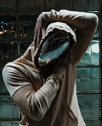 human person in chrome mask and pullover hoodie behind clear glass wall person