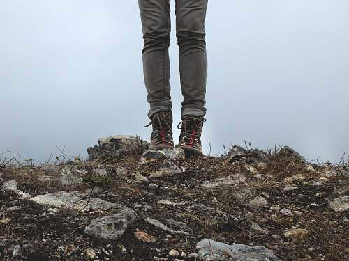 human person in gray jeans standing on rocks during daytime person