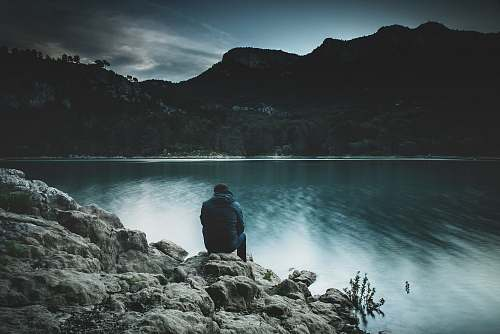 person person sitting on rock near body of water human