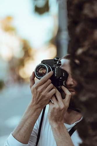 human person using black Nikon DSLR camera camera