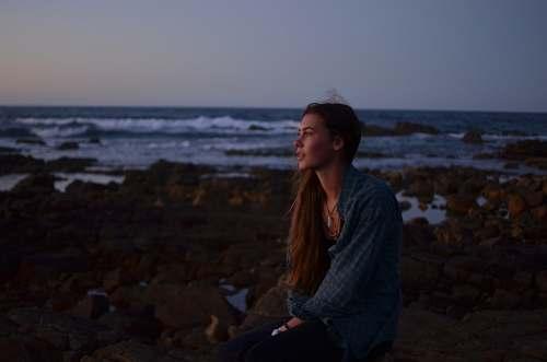 person photo of woman sitting on rocks near beach human