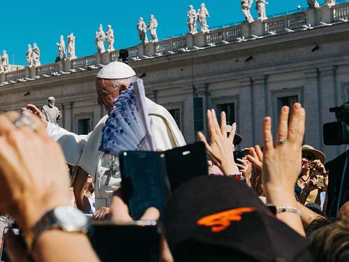 person Pope surrounded with people during daytime human