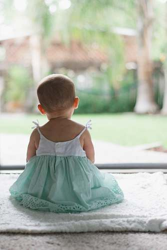 human selective focus photo of toddler wearing sleeveless dress sitting on floor baby