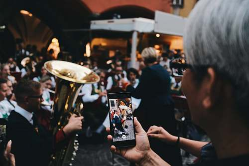 human selective focus photo of woman holding phone taking a photo of man playing instrument person