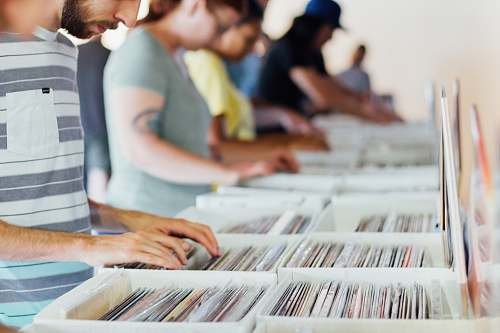 person selective focus photography of group of people selecting vinyl record sleeves human