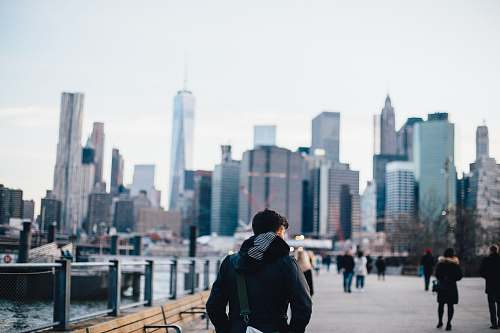 person selective focus photography of man standing near body of water walking towards buildings human