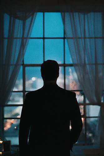 person silhouette of person standing against windowpane human