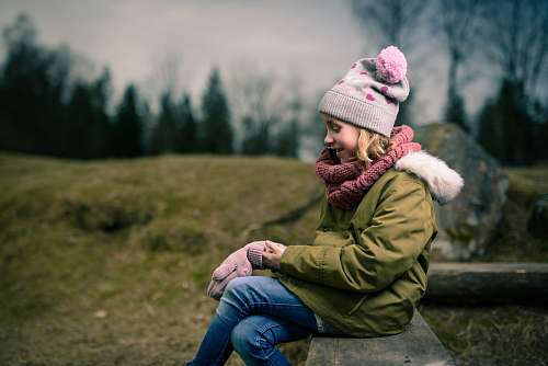 human smiling girl sitting on brown bench person