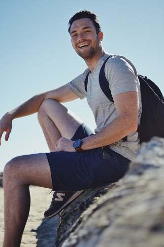 human smiling man sitting on gray rock at daytime person