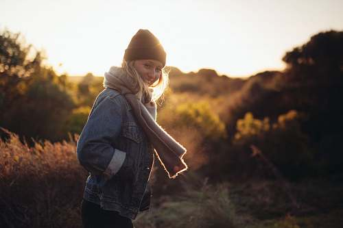 human smiling woman taking photo near trees and brown grass during sunrise person