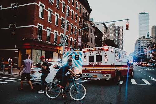 person three people walking near man riding bicycle on street near ambulance human