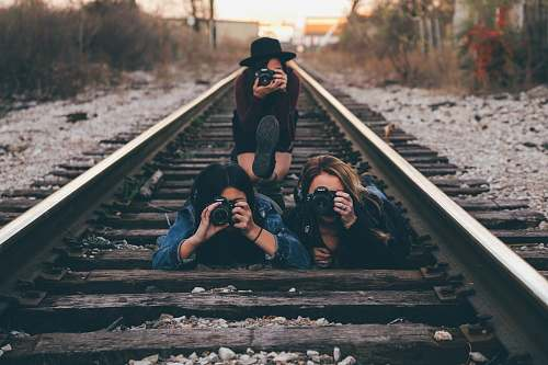 human three women in train railway taking picture photographer