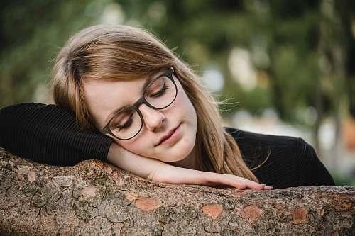 person tilt shift photography of woman sleeping on log human