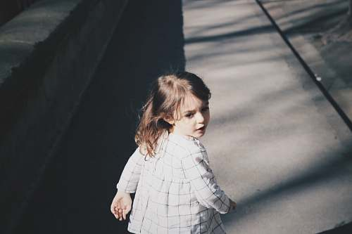 person toddler girl walking on gray concrete road at daytime human