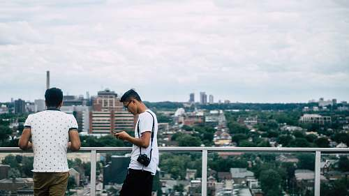 human Two men are on a balcony overlooking the Toronto cityscape. person