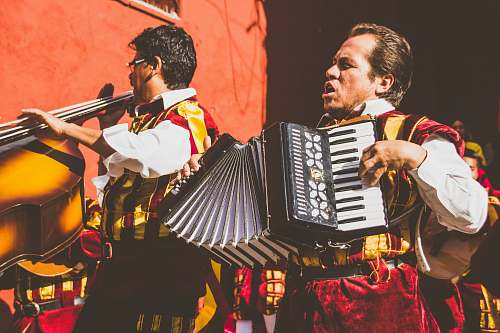 human two men playing cello and accordion beside red building photo music
