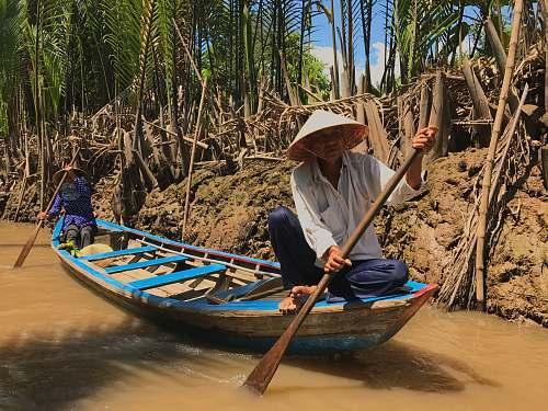 person two men riding canoe on bridge boat