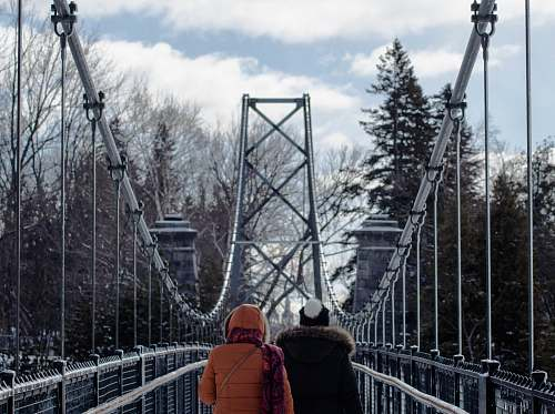 person two persons walking on gray suspension bridge in between trees at daytime human