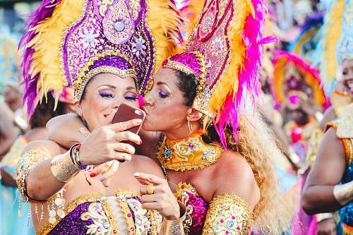 human Two women Carnival dancers pose for a selfie as one kisses other on the cheek. festival
