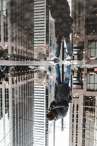 person water mirror reflection photography of man standing on pavement front of buildings human
