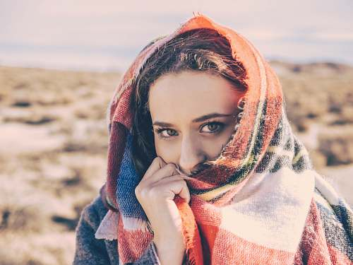 person woman covering her face with red and white scarf human