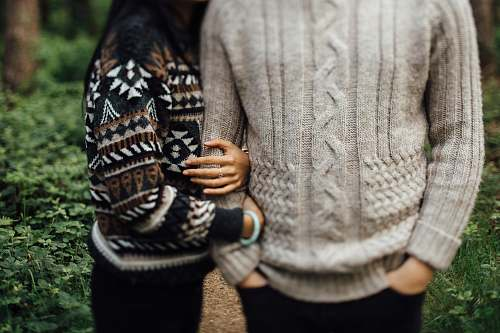person woman in black and white sweater hugging man in gray cable knit sweater sweater