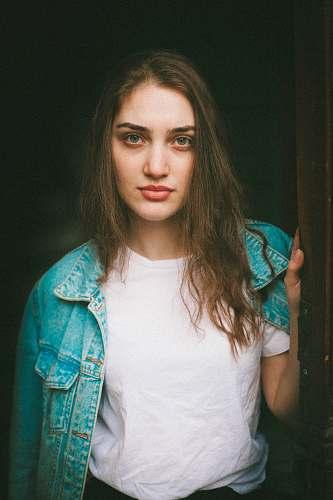 person woman in blue denim jacket holding door human