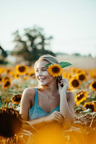 human woman in blue sleeveless dress holding sunflower placing in ear person
