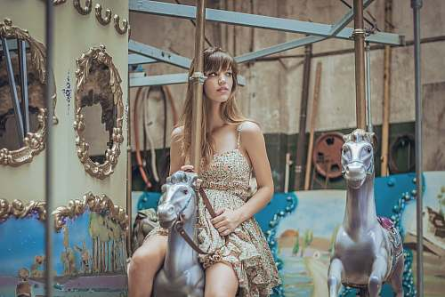 person woman in gray floral dress riding carousel human