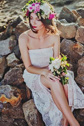 human woman in white tube dress sitting on rock wedding