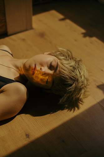 person woman lying on brown wooden surface human