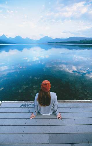 person woman sitting in front of calm body of water human