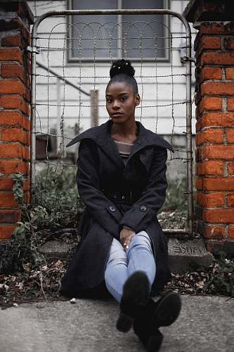 person woman sitting near grey gate brick