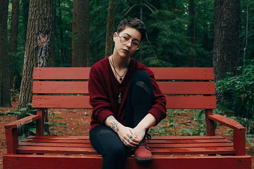 human woman sitting on bench near forest person