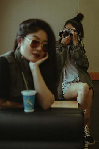 person woman sitting on chair while taking photo cup