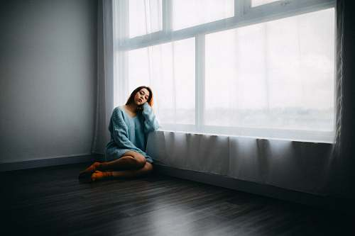 person woman sitting on floor near window human