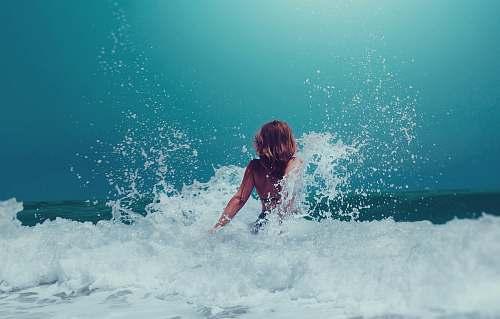 human woman sitting on seashore person